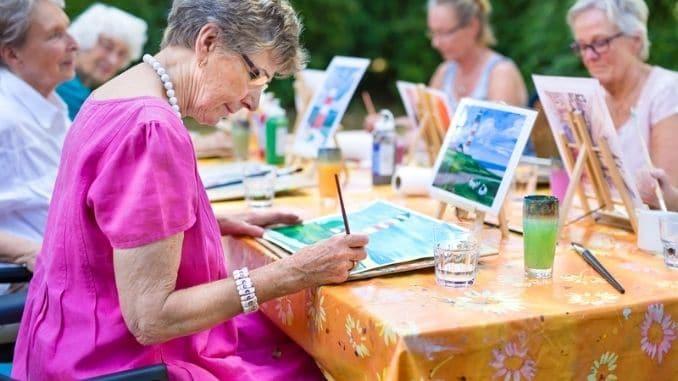 Stylish senior lady painting