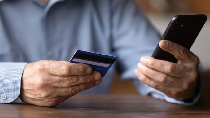 senior man holding phone and credit card