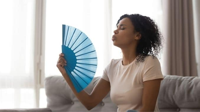 cools herself with fan